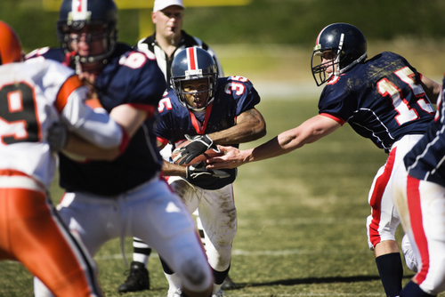 A child playing football with the proper protective mouth guard on from Diers Orthodontics in Cincinnati, OH